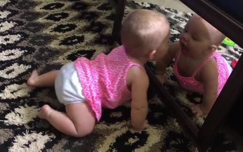 Baby repeatedly kisses her mirror reflection