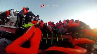 Panicked Migrants Scramble onto Italian Coast Guard Dinghies - Video