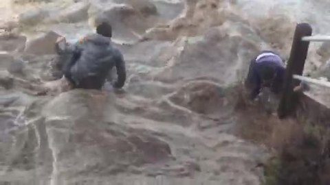 Men almost swept away by massive wave