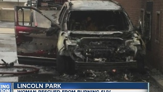 Woman rescued from burning SUV - Video