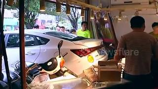 Three people injured after car reverses into shop in China - Video
