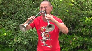 'Kung-fu master' carries buckets with his eye sockets while playing instrument through his nose - Video