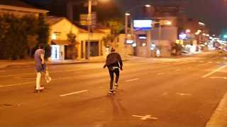 Skaters Glide Down a Deserted Sunset Boulevard - Video