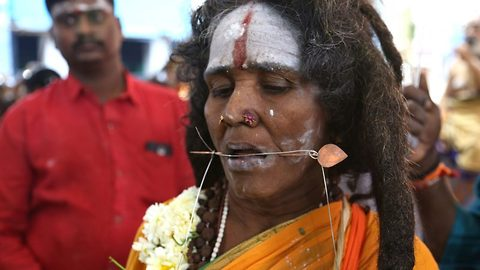 Stunning pictures show hundreds of hindu devotees honour 'god of war' with bodies pierced with metal hooks and skewers
