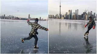 Man performs ice skating tricks on frozen Toronto lake