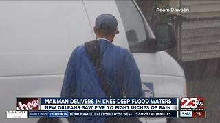 Mailman treads through knee deep water to deliver mail