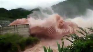 Water gushes over dam near scene of Laos flooding disaster