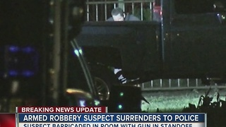 Armed robbery suspect surrenders after all night standoff - Video