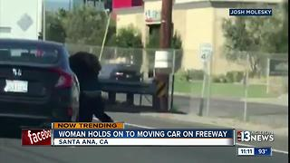 Woman holds on to moving car on freeway - Video