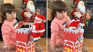 Baby has adorably priceless reaction to Santa Claus toy
