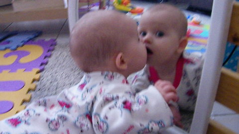 Baby crawls to mirror, embraces her reflection