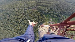 Incredible moment daredevil hangs off 350m tall platform using just one hand - Video
