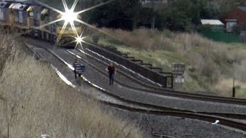 Freight Train Narrowly Misses Youths Playing on Tracks