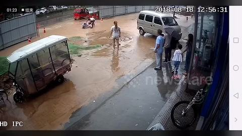 Two girls fall into pit covered by floodwater