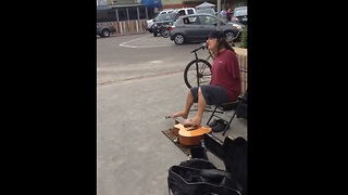 Street performer plays guitar with his feet - Video