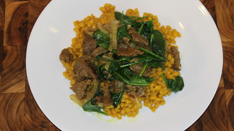 Turmeric barley with caramelized onion, beef and spinach