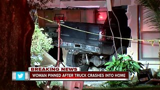 Woman pinned after truck crashes into home