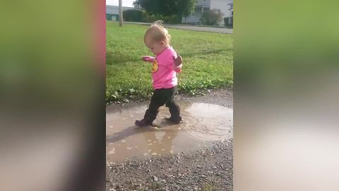 A Tot Girl Runs Into The Bumper Of A Car While She Walks In Puddles