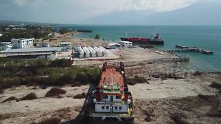 Drone footage shows large ship swept onto land by force of Palu tsunami