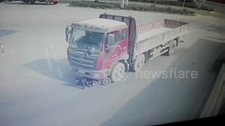 Scooter driver miraculously survives being dragged by lorry - Video