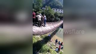 Suspension bridge tips over sending tourists into river - Video