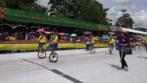 Adorable moment dozens of Thai schoolgirls dance on unicycles at Buddhist festival