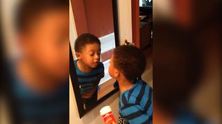 Boy Adorably Confused By Reflection In Mirror - Video