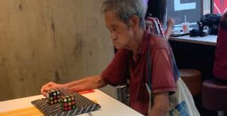 Man solves two Rubik's cubes without looking