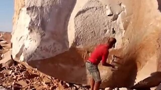 Man manages to split this massive stone with ease