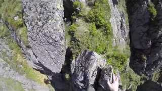 Mountain Runner Free Climbs Narrow Rocky Outcrop