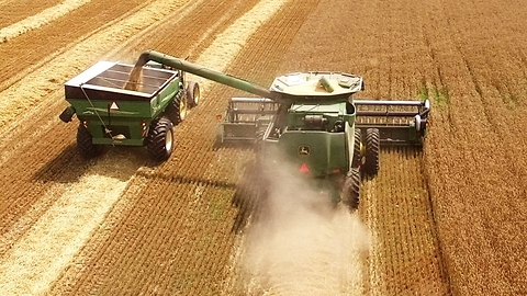 Farming Machines Work In Harmony To Harvest Crops