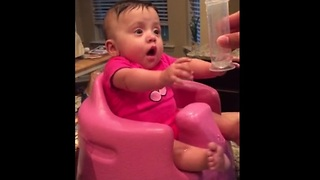Baby hilariously freaks out over cup of water - Video