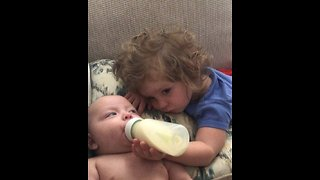 Sweet Toddler Diligently Feeds Her Baby Brother - Video