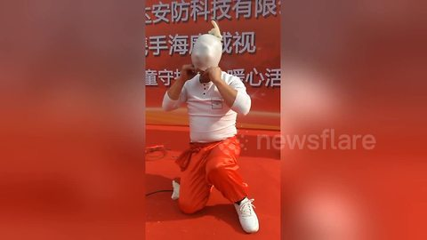 Chinese performer inflates plastic glove with nose