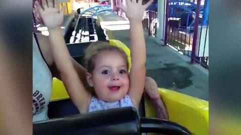 A Tot Girl Is Excited And Shocked As She Rides Her First Roller Coaster