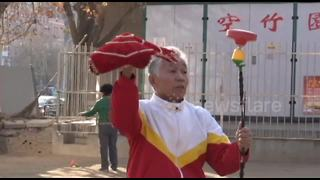 Elderly Chinese man plays diabolo on unicycle - Video