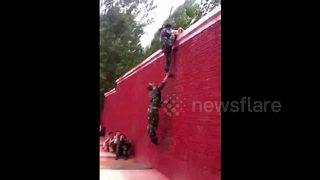 Three Men With Ninja-Like Skills Use Teamwork To Climb Up A High Wall - Video