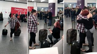 Loved-up woman surprises girlfriend with proposal at airport arrivals surrounded by hundreds of passengers - Video
