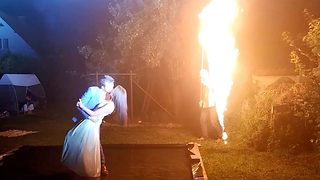 Flaming hot wedding portrait shows embracing couple kissing in front of wall of fire - Video
