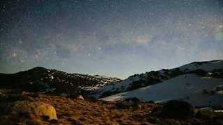 Clear Skies Reveal Bright Galaxies Over Snowy Mountains - Video
