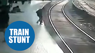 Moment a man miraculously walked away unharmed - despite lying under a TRAIN - Video