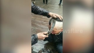 Chinese barber uses sickle to cut hair in China - Video