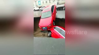 Cars drop into sinkhole caused by road collapse - Video