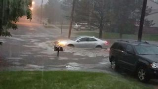 Car Drives Through Flooded Michigan Street - Video
