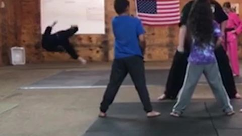 Guy Falls in The Background of Karate Practice Video
