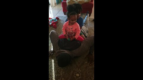 Dad attempts push-up challenge with kids on his back