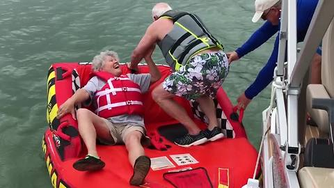 An Old Couple Tries To Get On Inflatable Tube