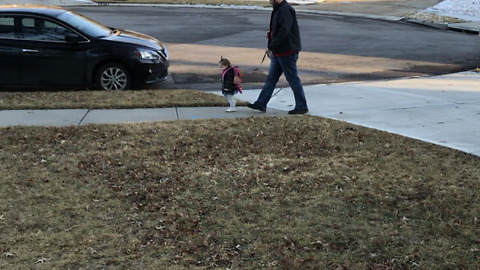 Dad walks his daughter on a leash