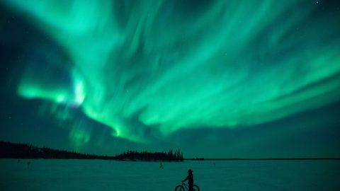 No need to worry about your brake light being out – Cyclists' path illuminated by stunning northern lights display