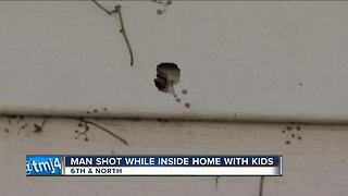 Stray bullet hits man feeding baby in home during shootout - Video